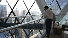 Business man and woman looking over city before returning to work. High quality Stock Footage