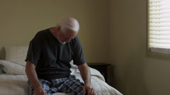Elderly man with pain sitting on bed Stock Footage