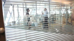 Candid view through blinds of office of workers talking in large business Stock Footage
