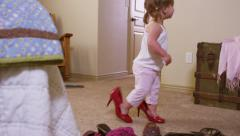 Cute young girl trying on mommy's shoes Stock Footage
