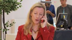 Strong and confident businesswoman struggles to keep her cool on a phone call - stock footage