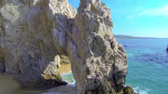 Stock Video Footage of Cabo Arch aerial boom up back side revealing waiting sailboat at lands end