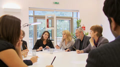 Diverse group of business people in a boardroom meeting, seated around a Stock Footage