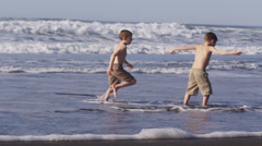 Two boys running in ocean together, slow motion Stock Footage
