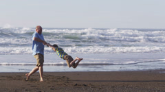 Father swinging son at beach Stock Footage