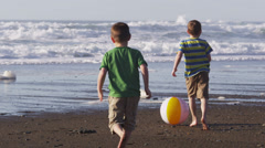 Two boys playing with beach ball, slow motion - stock footage