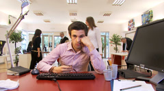 Bored male office worker struggles to stay awake at his desk. Stock Footage