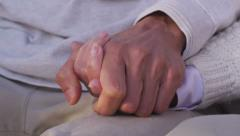 Closeup of senior couple holding hands - stock footage