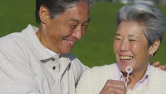 Happy senior couple at park blowing bubbles together - stock footage