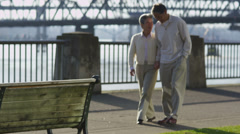 Senior couple sit together on bench at waterfront park Stock Footage