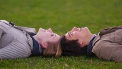 Young couple laying in grass pointing at clouds Stock Footage