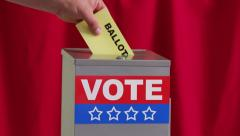Hand putting vote into ballot box Stock Footage