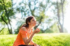 Young woman blowing on a dandelion Stock Photos