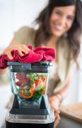 young woman preparing vegetables in the blender - stock photo