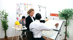 Architects or engineers in creative office looking at design plans - stock footage