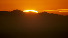 Sun setting behind mountains Stock Footage