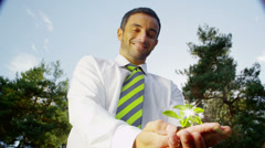 Businessman holding seedling plant. Green shoots environmental business concept Stock Footage