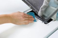 removing the lent out of dryer air filter screen - stock photo