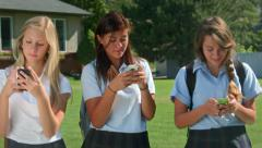 Three Pretty Uniformed Teen School Girls Standing, Texting (pans R to L) Stock Footage