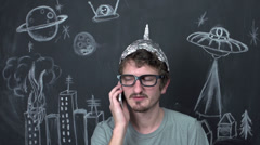 Paranoid alien conspiracy theorist on phone - stock footage