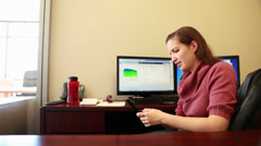 Woman texting while working in office Stock Footage