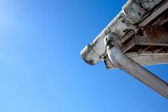 Upward view of mouldy asbestos guttering and downpipe Stock Photos