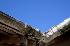 Upward view of corner of mouldy neglected asbestos guttering Stock Photos