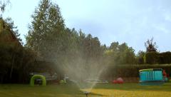 Fountain shower watering the lawn on a sunny summer day. Happy kids play Stock Footage