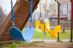 bright yellow and blue chain swings on kids playground - stock photo