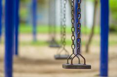 row of chain swings on kids playground - stock photo