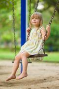 adorable girl swinging on kids playground - stock photo