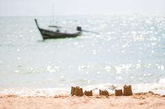 sand castle on beach of tropic sea with boat on back - stock photo