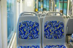 Blue seat places in modern city trolley bus on back side Stock Photos