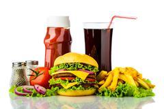 Cheeseburger, french fries, drink and ketchup Stock Photos