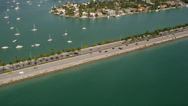 Stock Video Footage of Wide aerial shot of medium traffic on the MacArthur Causeway, tilt up revealing
