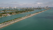 Stock Video Footage of Wide aerial shot flying by the MacArthur Causeway with medium traffic and Palm