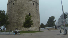 Morning traffic, White Tower of Thessaloniki, seagull and people Stock Footage