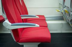 rows of seats with headrests and armrestes in modern suburb commuter train - stock photo