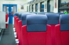 corridor with rows of seats with headrests in modern suburb commuter train - stock photo