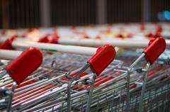 Handlebars of shopping carts in row near supermarket Stock Photos