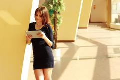 Stock Photo of young beautiful female student standing at unviersity campus with tablet comp