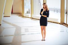 Businesswoman talking on phone standing in office hall Stock Photos
