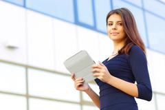 smiling businesswoman using electronic tablet outside - stock photo