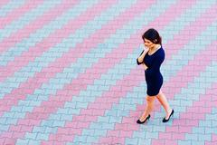 young attractive businesswoman talking on phone while walking across the stre - stock photo