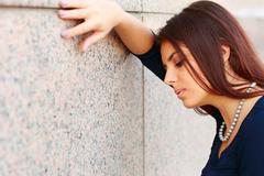 portrait of tired businesswoman leaning at the wall - stock photo