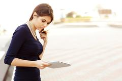 Smiling businesswoman using electronic tablet outside Stock Photos