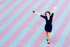 full-length shot of a cheerful beautiful businesswoman in formal dress outdoo - stock photo
