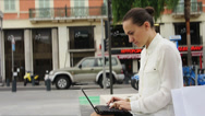 Stock Video Footage of Young business woman with laptop sitting in urban environment HD