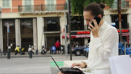 Stock Video Footage of Business woman with laptop and mobile phone sitting in urban environment HD