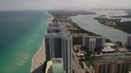 Stock Video Footage of Wide aerial shot flying by Trump Tower and following Collins Avenue while